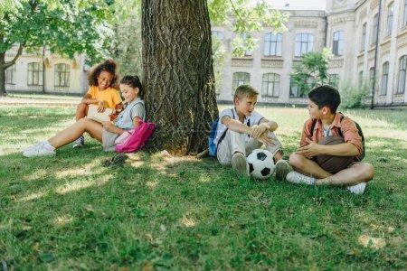 Foto de Cuatro lindos escolares multiculturales sentados en el césped y el árbol, hablando y leyendo libros - Imagen libre de derechos