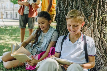 Photo for Adorable schoolchildren sitting on lawn and reading books near multicultural friends - Royalty Free Image