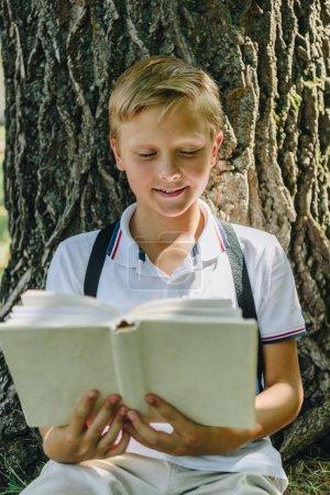 Photo pour Adorable écolier souriant assis près de l'arbre et le livre de lecture - image libre de droit