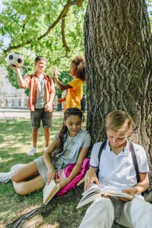 Photo for Adorable schoolkids sitting under tree and reading books near multicultural friends - Royalty Free Image