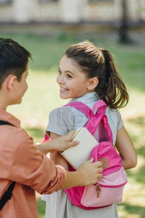 Photo pour Vue partielle du livre d'emballage d'écolier dans le sac à dos de l'écolière gaie - image libre de droit