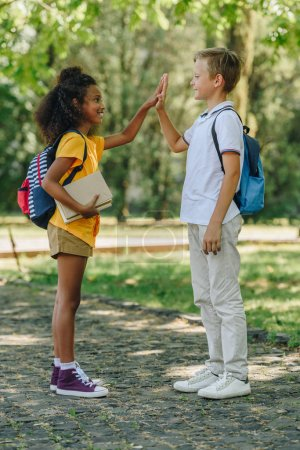Photo for Two smiling multicultural schoolkids giving hive five while standing in park - Royalty Free Image