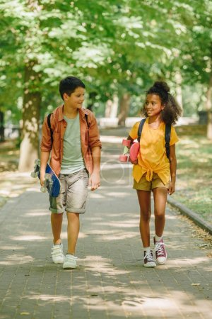 Photo for Two multicultural schoolkids walking in park while holding skateboards - Royalty Free Image