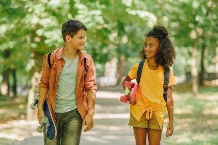 Foto de Dos niños de la escuela multicultural sonriente sando caminando en el parque mientras sostiene napatinetas - Imagen libre de derechos