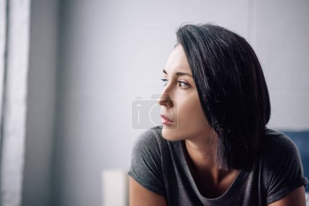 beautiful depressed woman looking away at home with copy space