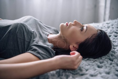 Photo for Beautiful depressed woman lying on bed at home - Royalty Free Image