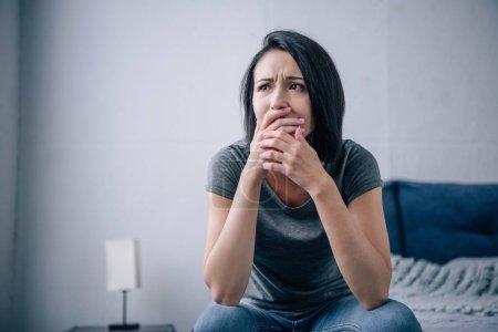 Photo pour Belle femme triste couvrant la bouche à la maison sur le lit - image libre de droit