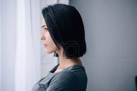 Photo for Beautiful depressed woman looking at window at home with copy space - Royalty Free Image