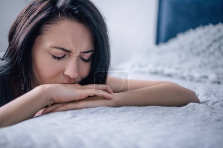 Photo for Beautiful depressed woman leaning on bed at home - Royalty Free Image