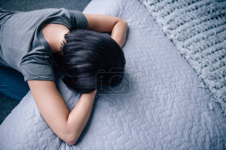 Photo for Top view of depressed woman lying on bed at home with copy space - Royalty Free Image