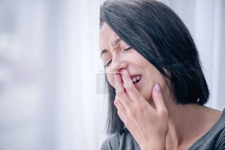 Photo for Selective focus of depressed brunette woman covering mouth and crying at home - Royalty Free Image