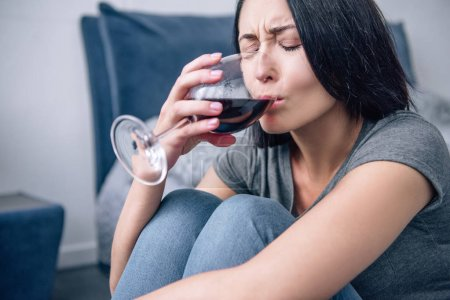 Photo for Beautiful depressed woman drinking wine at home - Royalty Free Image
