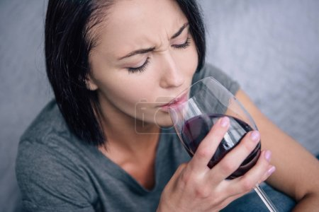 Photo for Lonely upset woman drinking wine at home - Royalty Free Image