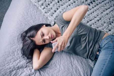 Photo for Lonely depressed woman on bed using smartphone in bedroom - Royalty Free Image