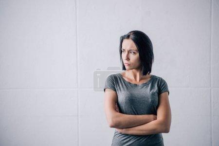 Photo pour Femme déprimée de brunette avec les bras croisés à la maison - image libre de droit
