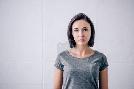 Photo for Sad brunette woman looking at camera at home - Royalty Free Image