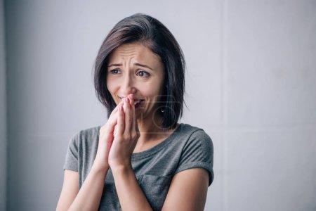 Photo pour Triste brunette femme couvrant la bouche et pleurant à la maison - image libre de droit
