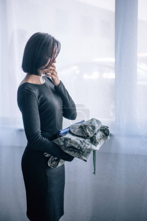 depressed woman holding military clothing at home