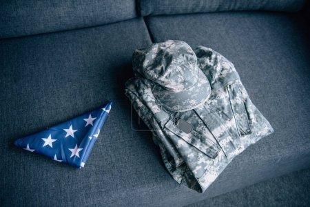 Photo pour Vêtements militaires et drapeau américain plié sur le canapé à la maison - image libre de droit