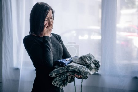 Photo for Upset crying woman holding military clothing at home - Royalty Free Image