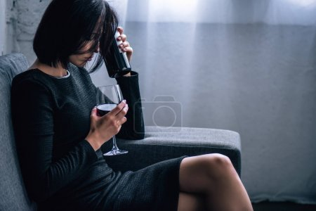 Photo for Depressed woman sitting on sofa with wine glass at home - Royalty Free Image