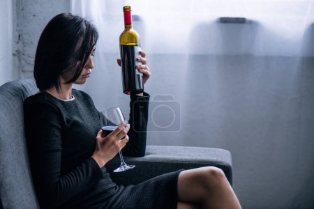 Photo for Depressed lonely woman with wine bottle and glass at home - Royalty Free Image