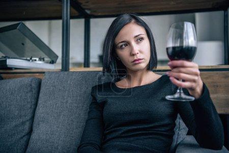 Photo pour Femme déprimée sur le canapé regardant le verre de vin à la maison - image libre de droit