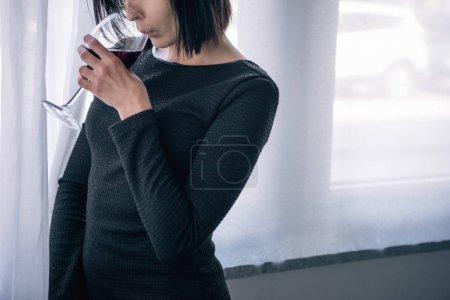 Photo for Cropped view of upset woman drinking wine at home - Royalty Free Image
