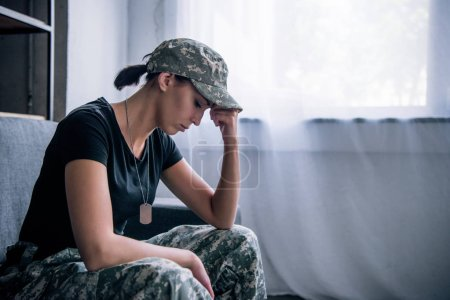 Photo for Depressed lonely woman in military uniform at home - Royalty Free Image