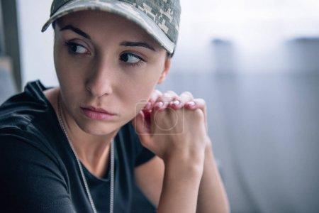 Photo pour Femme déprimée en uniforme militaire et casquette à la maison avec espace de copie - image libre de droit