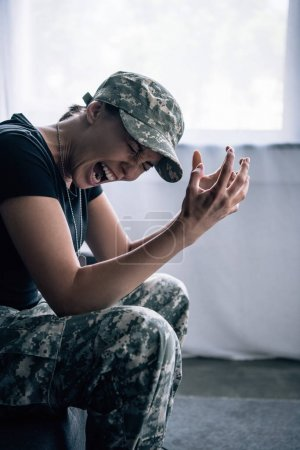 Photo for Depressed woman in military uniform sitting on couch and screaming at home - Royalty Free Image