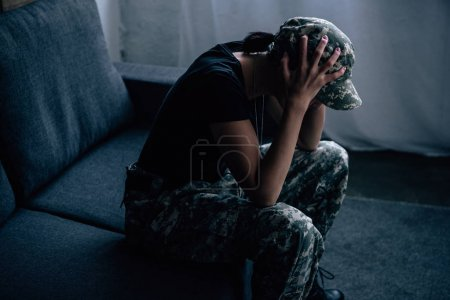 Photo for Depressed woman in military uniform with hands on head at home - Royalty Free Image