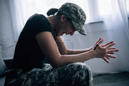 Photo for Depressed woman in military uniform screaming at home - Royalty Free Image