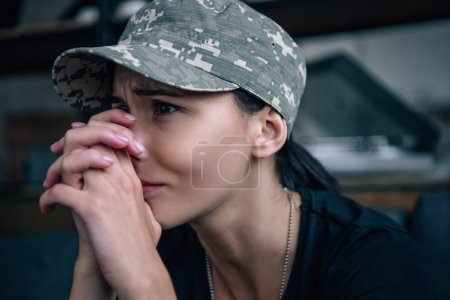 Photo for Depressed woman in military uniform crying at home - Royalty Free Image