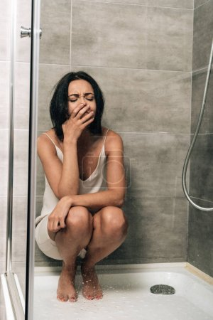 Photo pour Attractive depressed woman sitting and crying in shower at home - image libre de droit