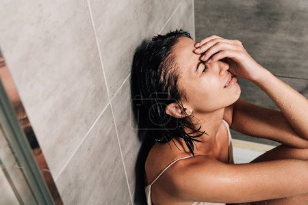 Photo for Sad depressed woman sitting in shower and crying at home - Royalty Free Image