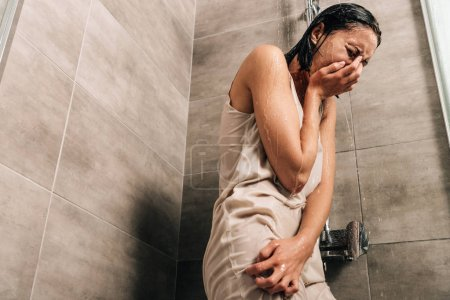 Photo for Lonely sad woman crying in shower at home with copy space - Royalty Free Image