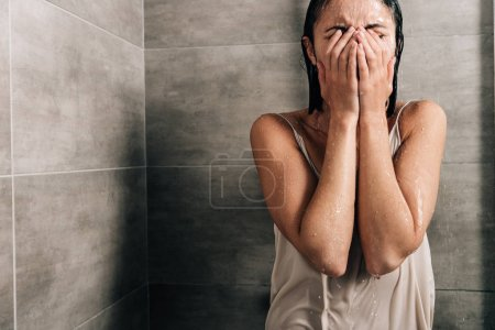 Photo for Lonely sad woman covering face and crying in shower at home with copy space - Royalty Free Image