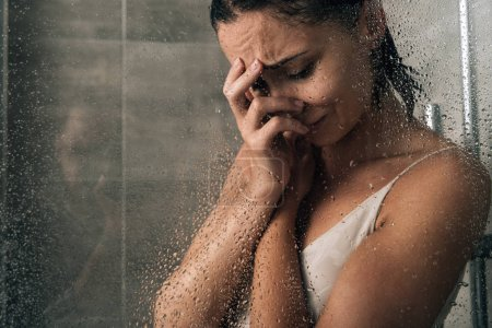 Photo for Beautiful sad woman covering face and crying in shower at home - Royalty Free Image