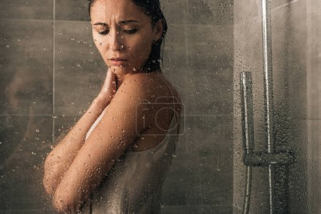 Photo pour Beautiful sad woman in shower at home through glass with water drops - image libre de droit