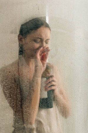 Photo pour Lonely depressed woman in shower with wine bottle at home - image libre de droit