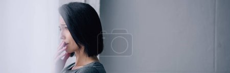 Photo for Panoramic shot of depressed brunette woman covering mouth at home with copy space - Royalty Free Image