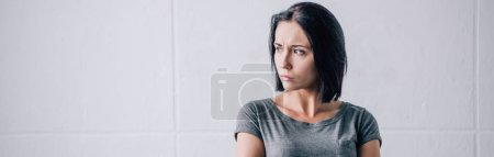 Photo for Panoramic shot of depressed brunette woman looking away at home - Royalty Free Image