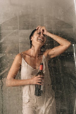 Photo pour Lonely depressed woman in shower holding wine bottle and crying at home - image libre de droit