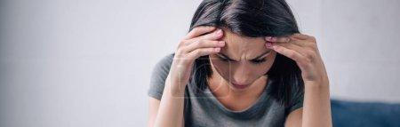 Photo pour Tir panoramique de la femme brune déprimée avec des mains sur la tête à la maison - image libre de droit