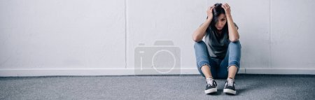 Photo for Panoramic shot of depressed brunette woman sitting on floor at home with copy space - Royalty Free Image