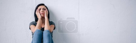 Photo for Panoramic shot of depressed brunette woman sitting on floor at home - Royalty Free Image