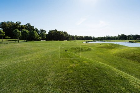 Photo pour Arbres verts près de l'étang contre le ciel bleu avec des nuages - image libre de droit