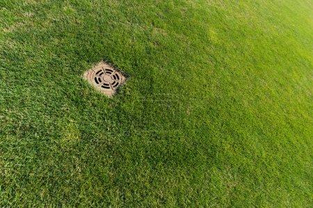 Photo pour Couverture métallique de trou d'homme sur l'herbe fraîche verte - image libre de droit