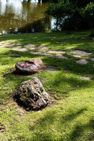 enfoque selectivo de piedras en hierba verde cerca del lago en el parque